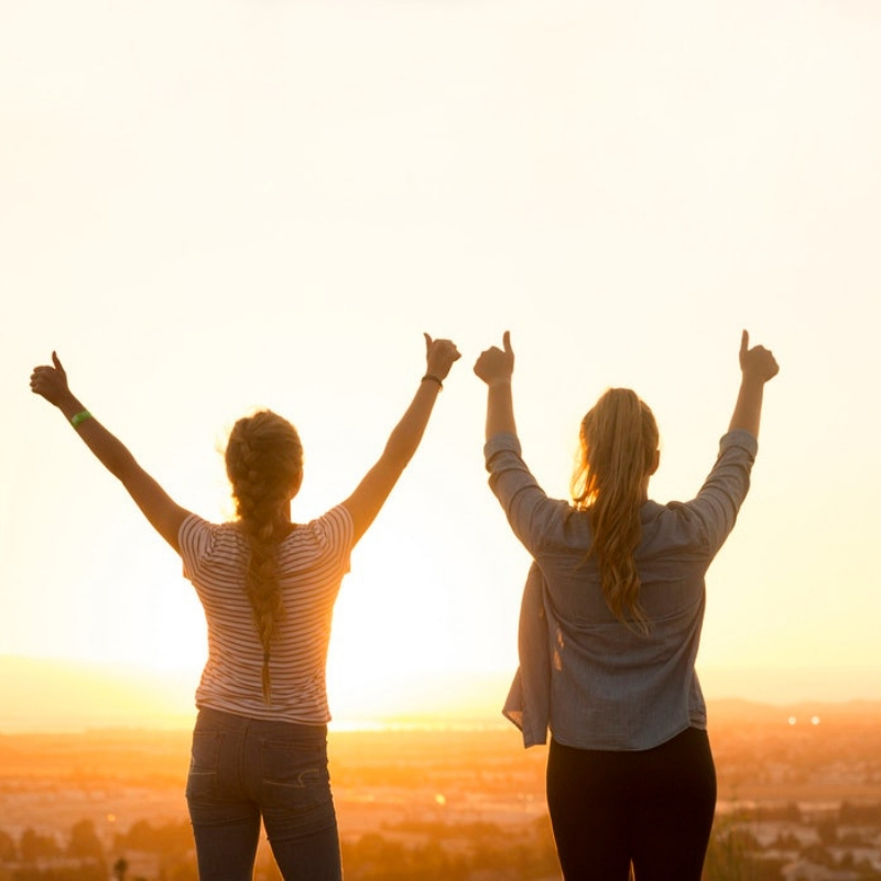 Two girls facing the sun holding their thumbs up