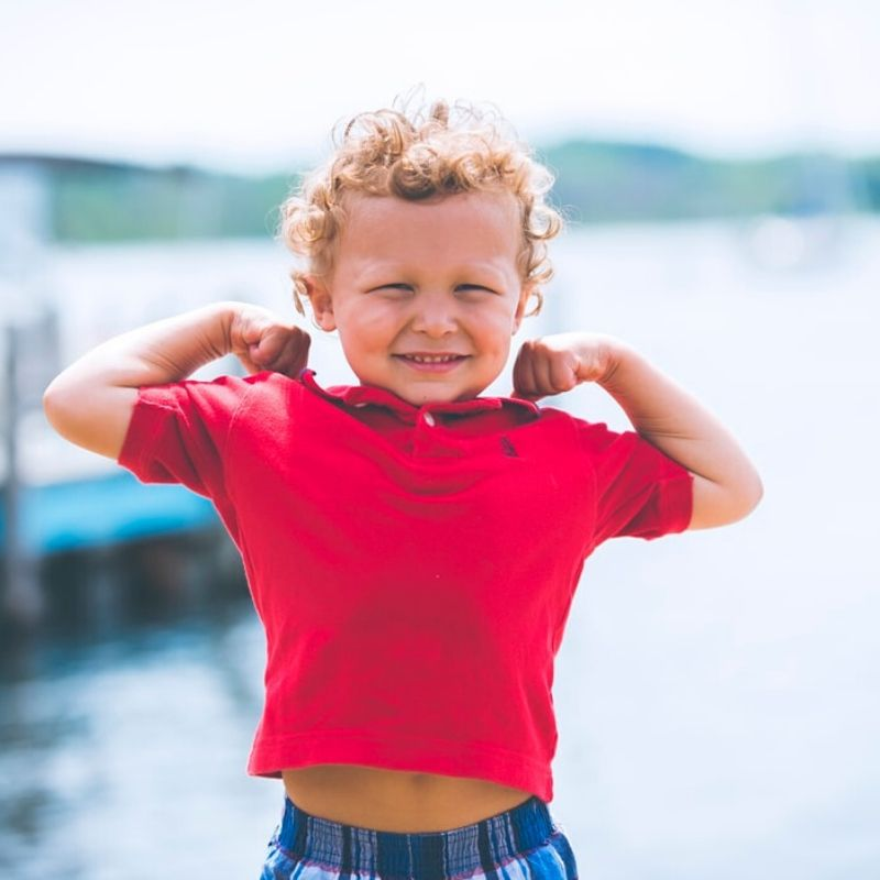 Young boy in red polo shirt showing his muscles