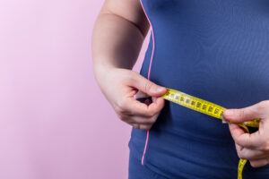 Overweight woman with measuring tape on waistline, closeup
